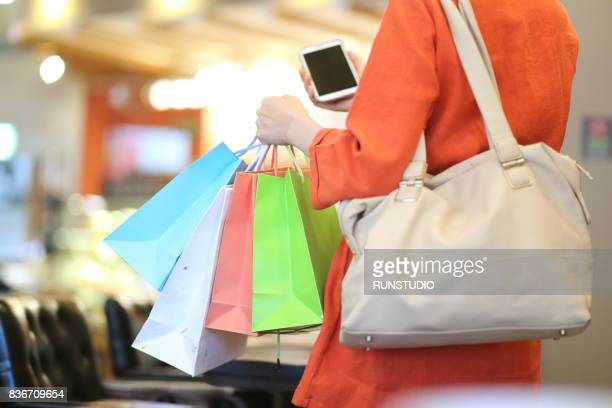woman using cell phone with shopping bags