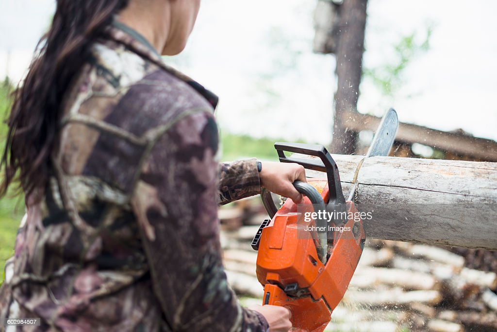 Woman using chainsaw : Stock Photo