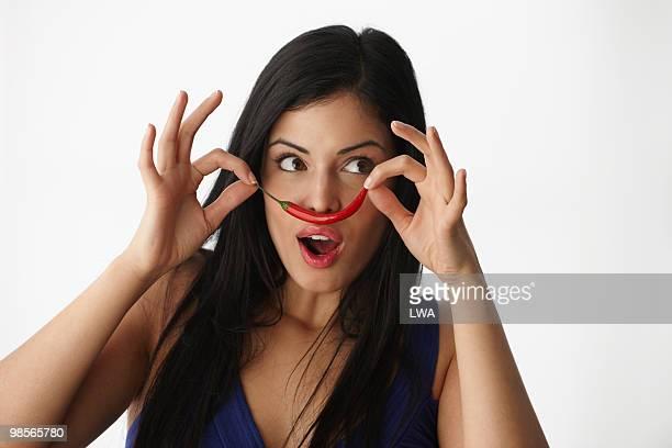 Woman Using Chili Pepper To Make Moustache