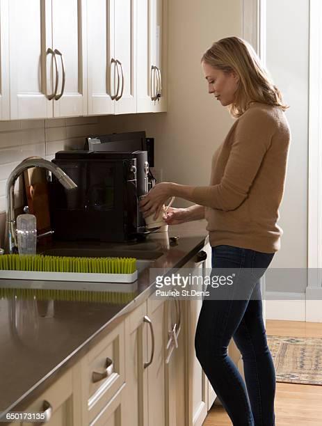 Woman using coffee machine in kitchen