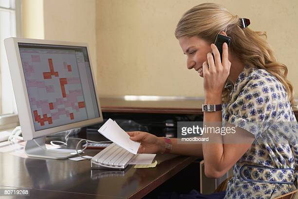 Woman Using Computer and Cell Phone