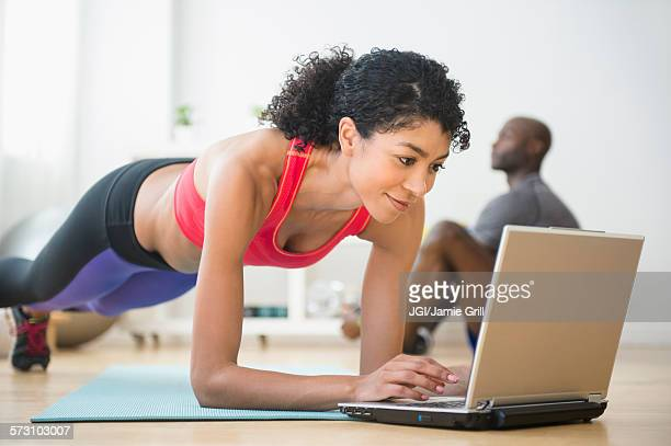 Woman using computer and doing push-ups in gym