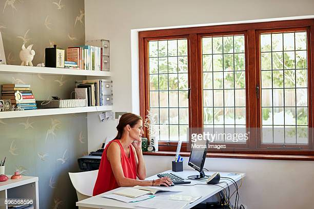 woman using computer and mobile phone at desk - remote work stock pictures, royalty-free photos & images