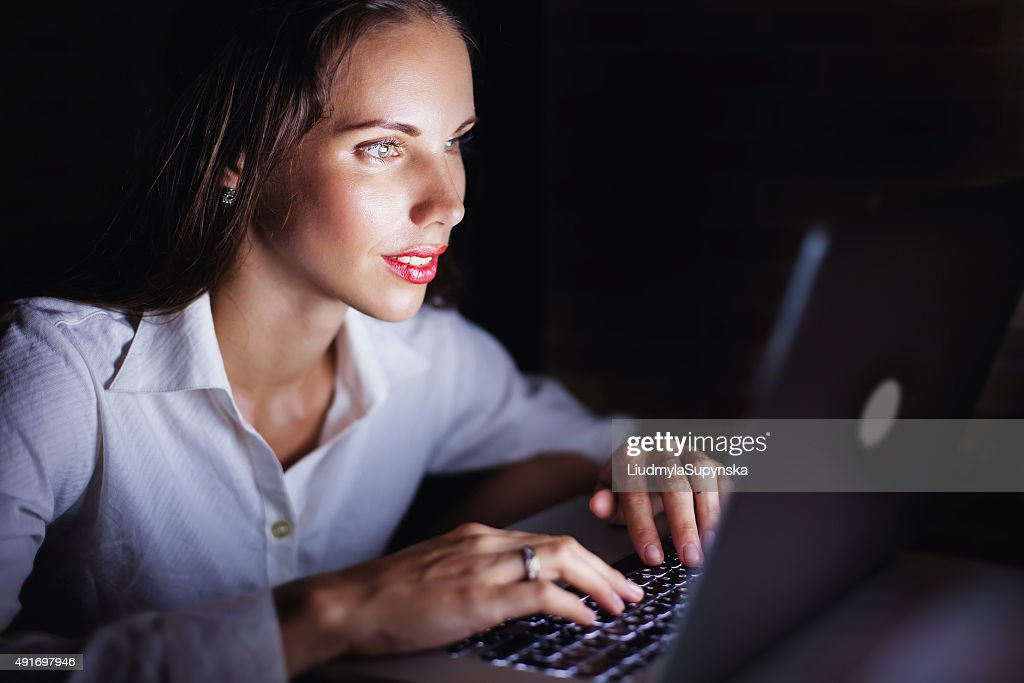 woman using computer late at night : Stock Photo