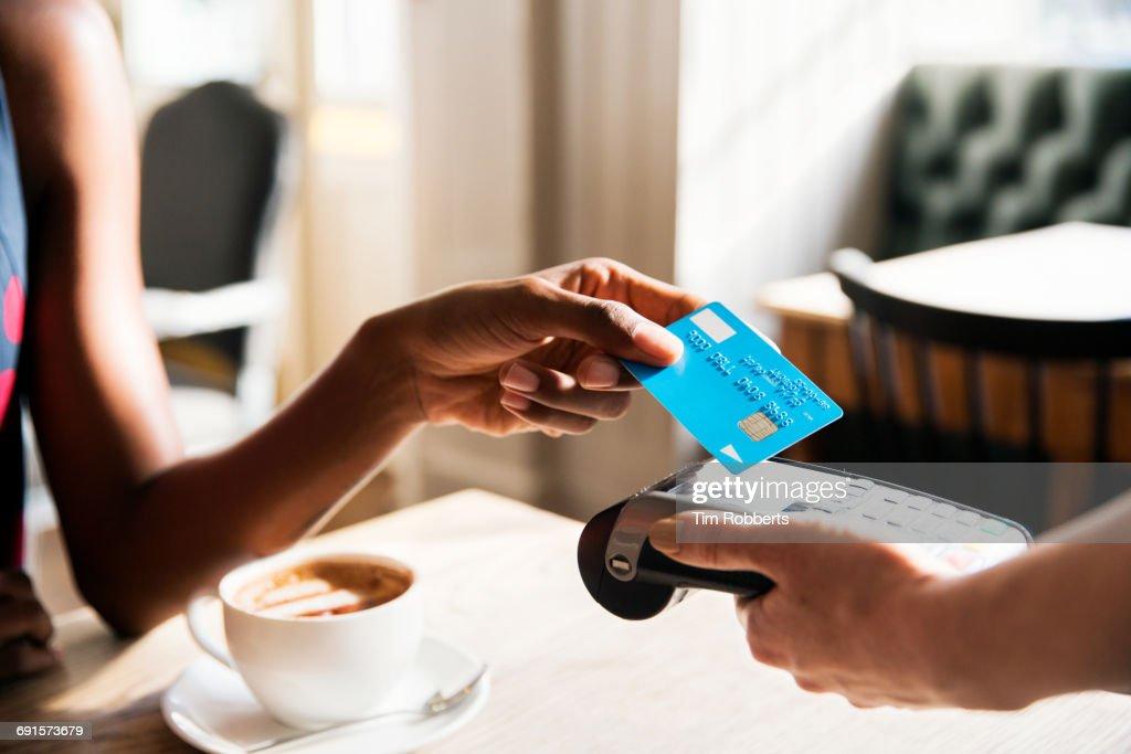 Woman using contactless payment, close up : Stock Photo