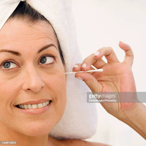 Woman using cotton swab in ear, close-up