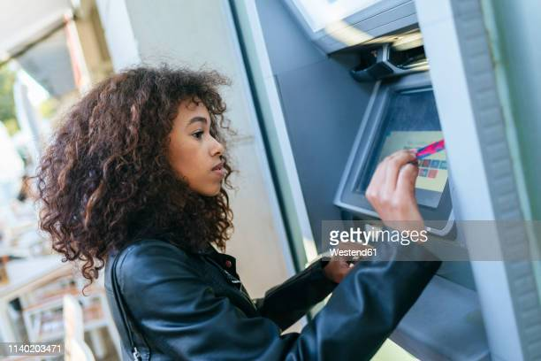 woman using credit card at atm - the image bank stock pictures, royalty-free photos & images
