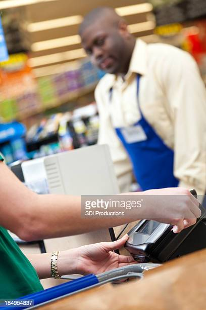 Woman using credit card at grocery store cash register