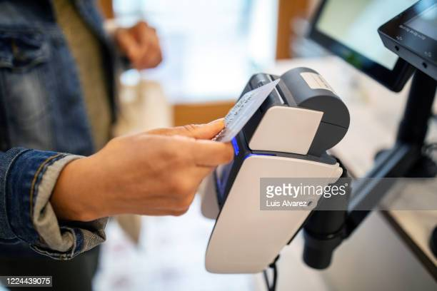 woman using credit card for contactless payment at checkout - consumerism stock pictures, royalty-free photos & images