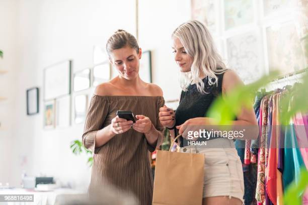 Woman using credit card reader by saleswoman