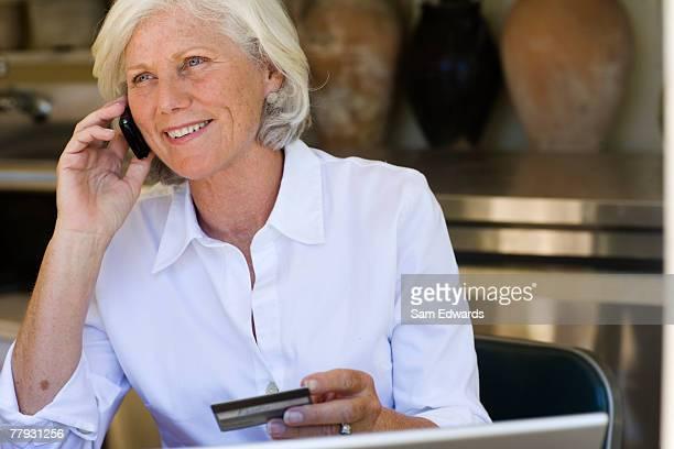 donna utilizzando la carta di credito per fare acquisti sul telefono - 55 59 anni foto e immagini stock