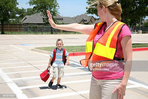 Woman Using Crosswalk Signals As Boy Crosses A Street