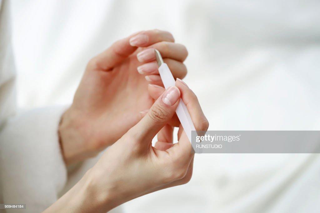 Woman using cuticle pusher : Stock-Foto