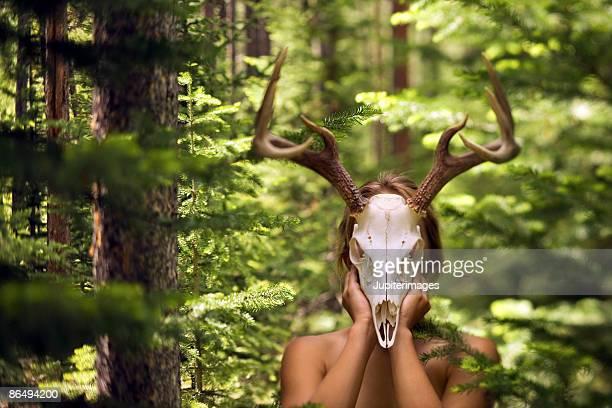Woman using deer skull as mask in woods