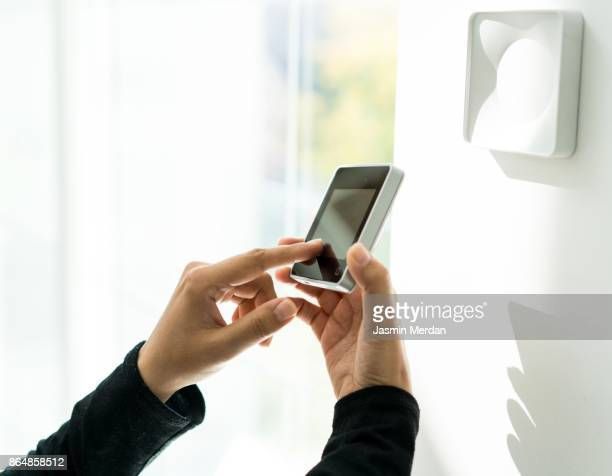 Woman using digital device high tech touch screen for smart home functions