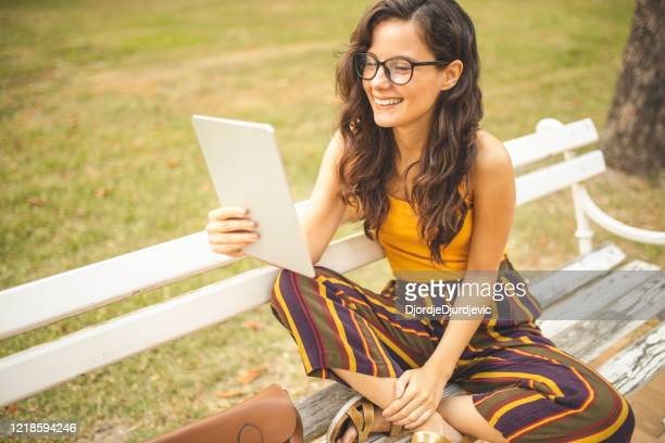 woman using digital tablet and sitting on park bench - free business coaching stock pictures, royalty-free photos & images