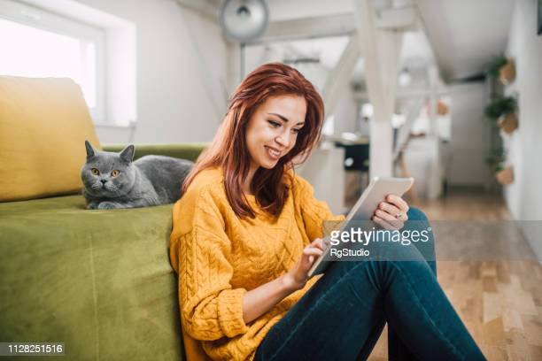 woman using digital tablet and smiling - undomesticated cat stock pictures, royalty-free photos & images