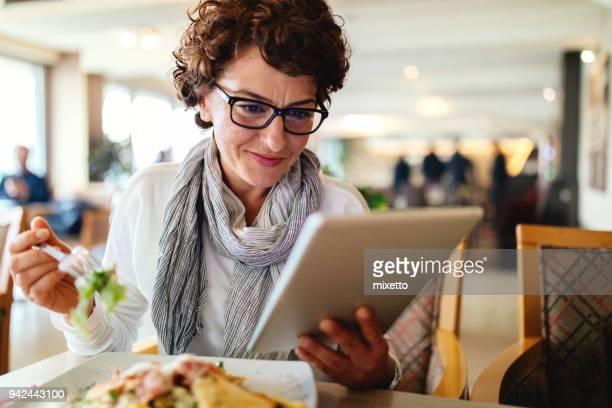 Woman using digital tablet at a restaurant