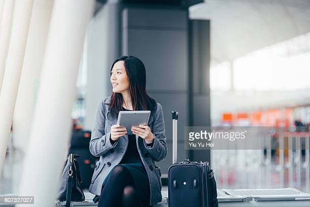 Woman using digital tablet at airport terminal