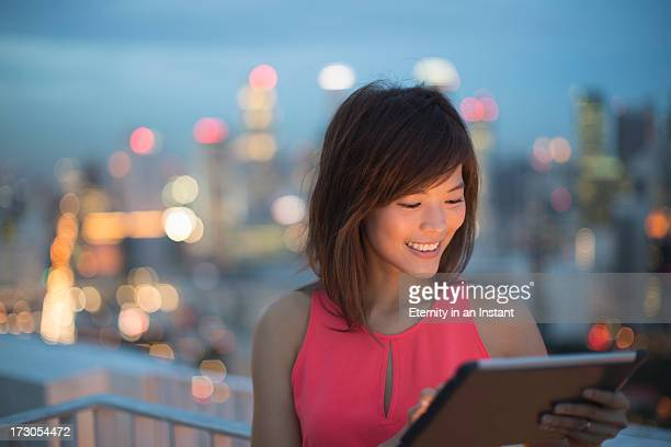 Woman using digital tablet at night in city