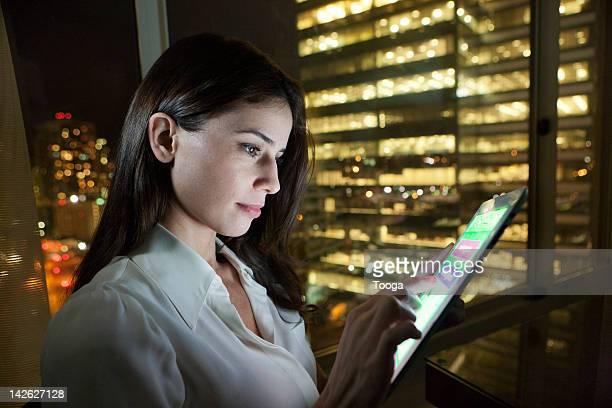 woman using digital tablet at night - mid adult women imagens e fotografias de stock