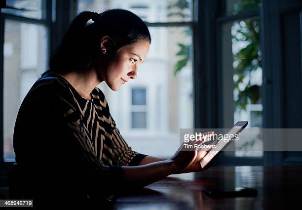 Woman using digital tablet at table.