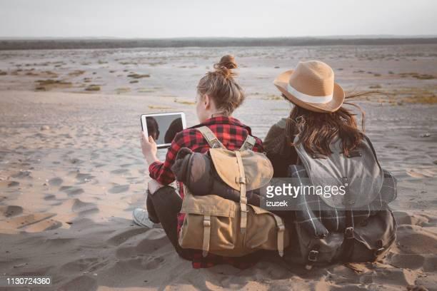 frau mit digitalem tablet von freund auf sand - jugendkultur stock-fotos und bilder