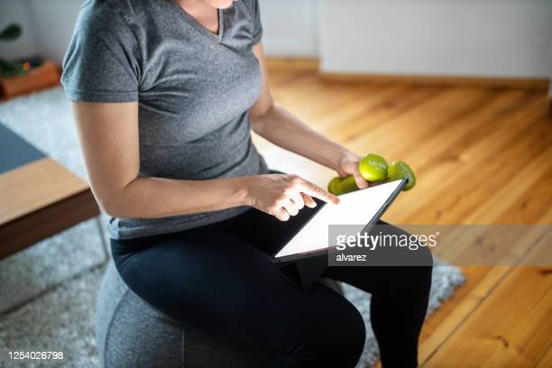 woman using digital tablet for doing exercising at home - hand weight stock pictures, royalty-free photos & images