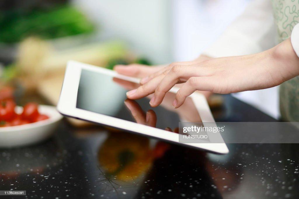 Woman using digital tablet for recipe : ストックフォト