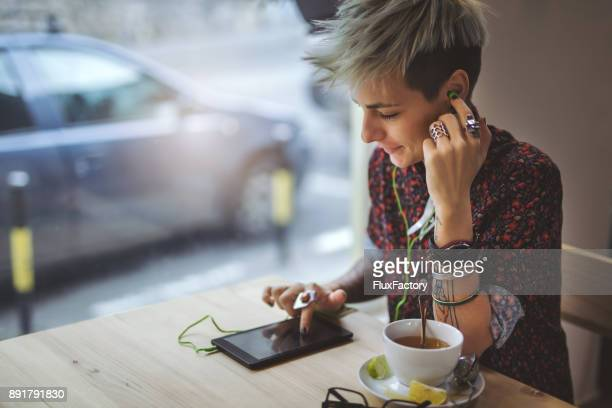 woman using digital tablet in a cafe - gender bender foto e immagini stock