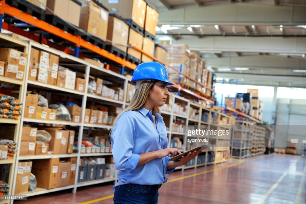 Woman Using Digital Tablet In A Distribution Warehouse Stock Photo