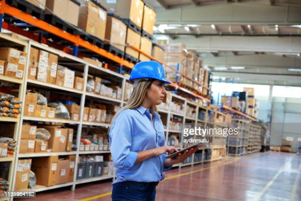 mulher que usa a tabuleta digital em um armazém de distribuição - lista - fotografias e filmes do acervo