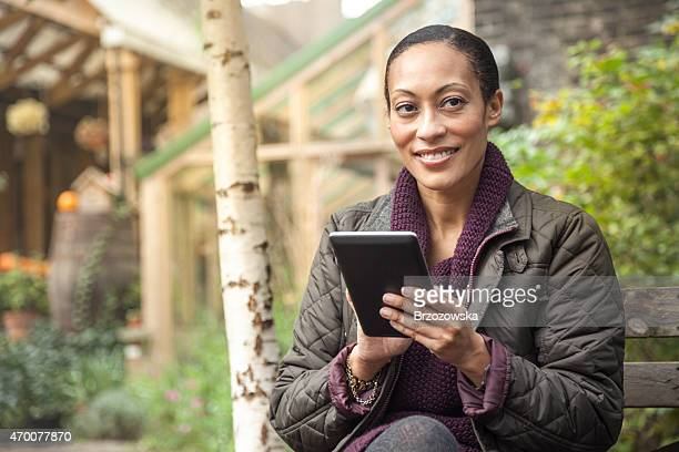 Woman using digital tablet in a garden (London, UK)