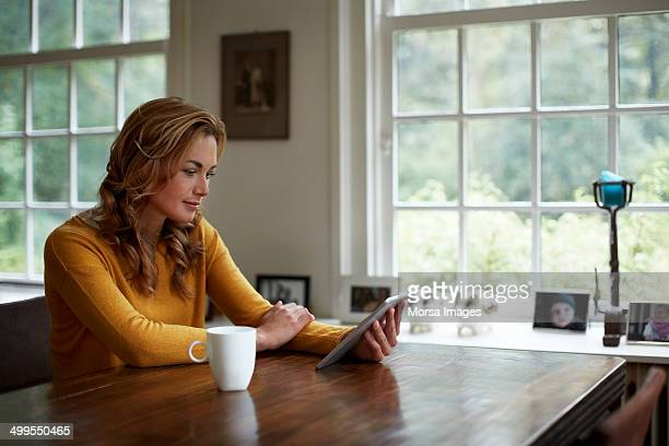 Woman using digital tablet in cottage