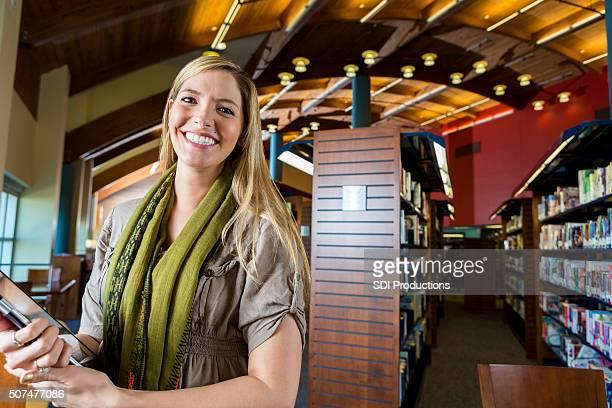 Woman using digital tablet in modern library