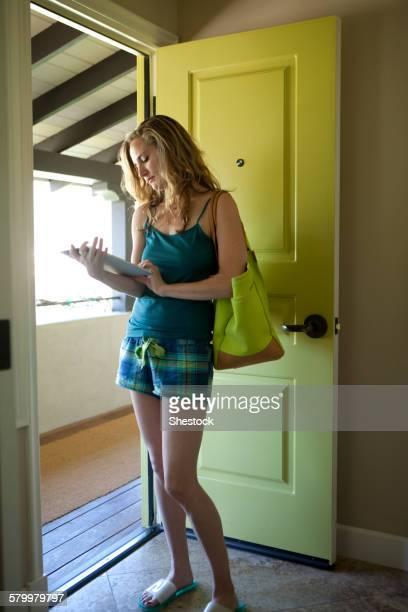 Woman using digital tablet in open doorway