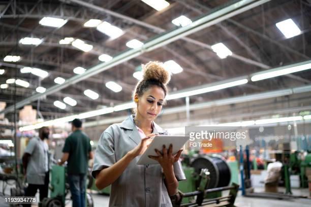 mulher que usa a tabuleta digital na indústria - indústria - fotografias e filmes do acervo