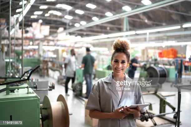 mujer que usa tabletas digitales en el retrato de la industria - mujeres de mediana edad fotografías e imágenes de stock