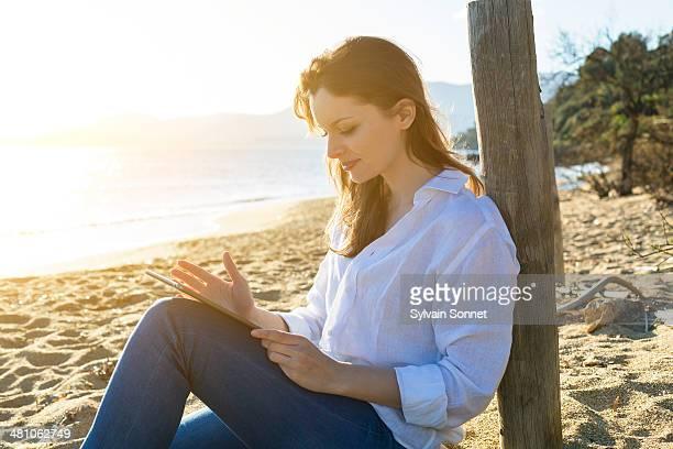 Woman Using digital tablet on Beach
