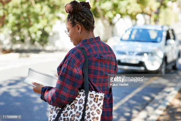 woman using digital tablet on roadside - 後ろボケ ストックフォトと画像