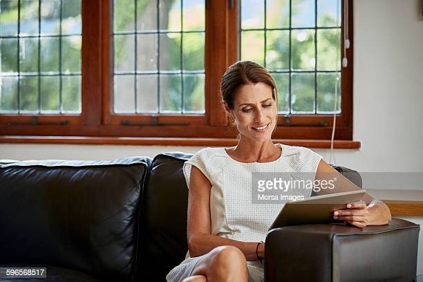 Woman using digital tablet on sofa at home