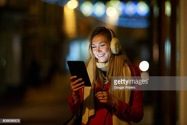Woman using digital tablet on street at night.