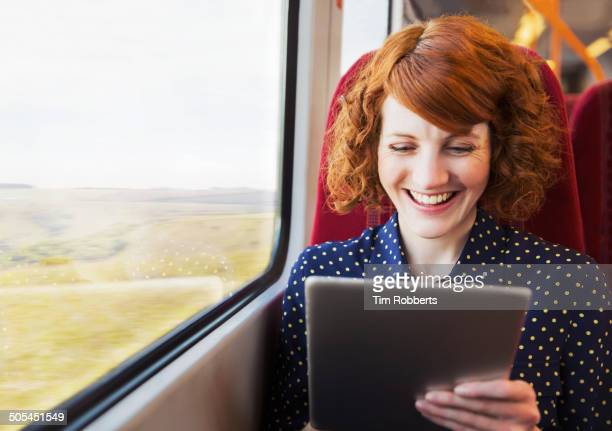 Woman using digital tablet on train.