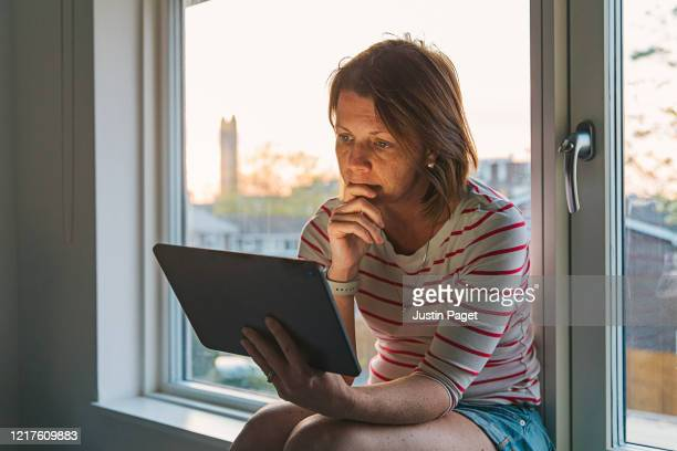 woman using digital tablet on window sill - solitude stock pictures, royalty-free photos & images