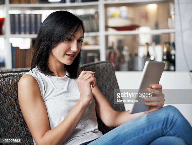 woman using digital tablet - sleeveless top stock pictures, royalty-free photos & images
