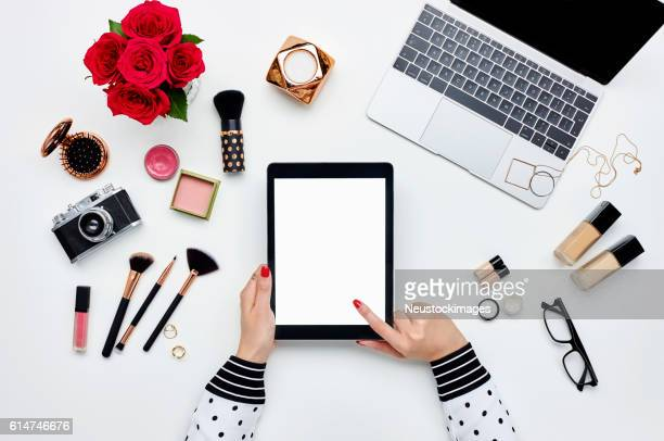Woman using digital tablet surrounded with beauty products and technologies