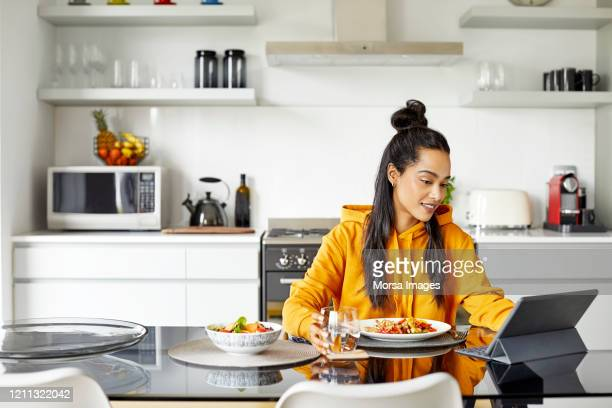 woman using digital tablet while having breakfast - lunch break stock pictures, royalty-free photos & images