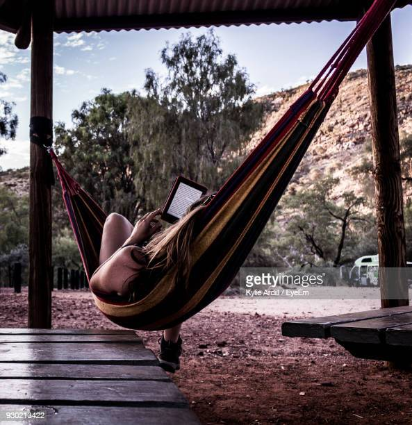 woman using digital tablet while relaxing in hammock - northern territory australia stock photos and pictures