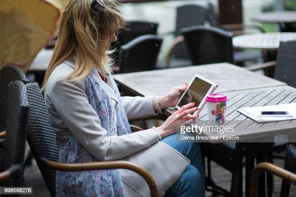 Woman Using Digital Tablet While Sitting At Table
