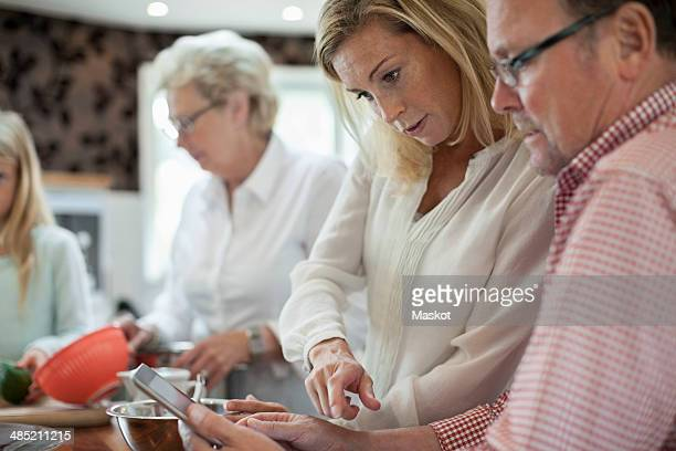 Woman using digital tablet with father-in-law while cooking in kitchen